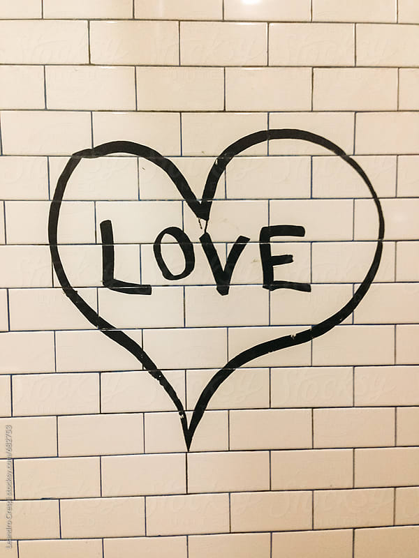 A heart with love word drawn in a tile wall by Leandro Crespi for Stocksy United