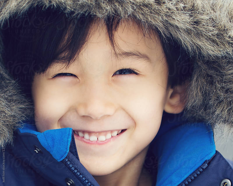 Close up image of smiling child in winter coat by kelli kim for Stocksy United