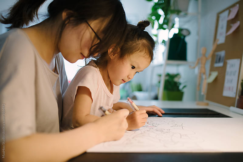 Adorable girl and her mother drawing at table by MaaHoo Studio for Stocksy United