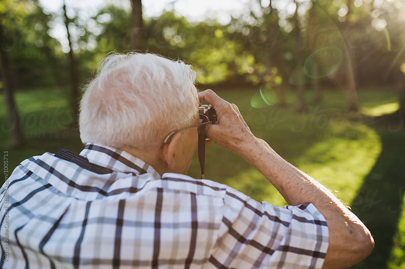 Old senior man taking pictures with old slr film camera by Rob and Julia Campbell for Stocksy United