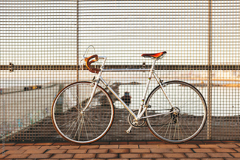 Vintage bicycle against a fence. by BONNINSTUDIO for Stocksy United