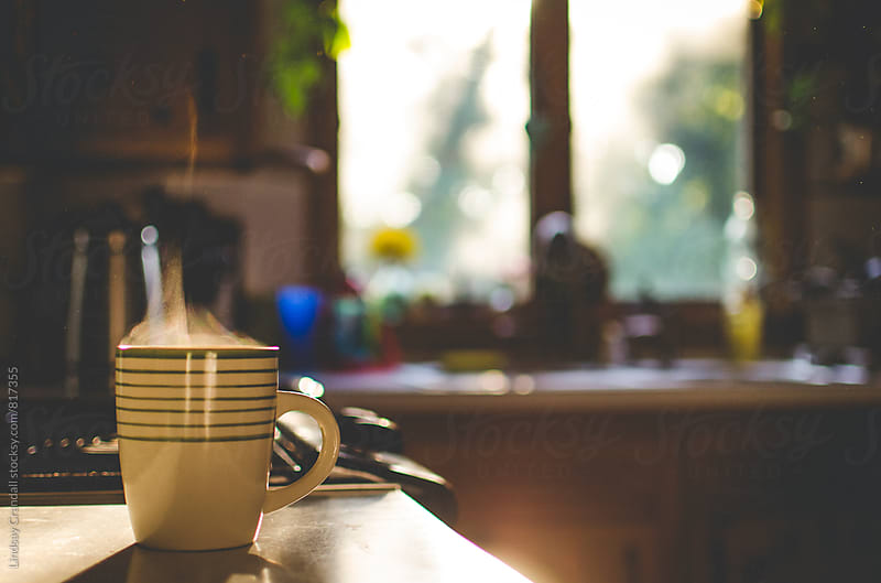 Steaming coffee mug on kitchen counter by Lindsay Crandall for Stocksy United