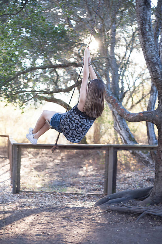 Young girl with long hair riding on a wooden rope swing by Carolyn Lagattuta for Stocksy United