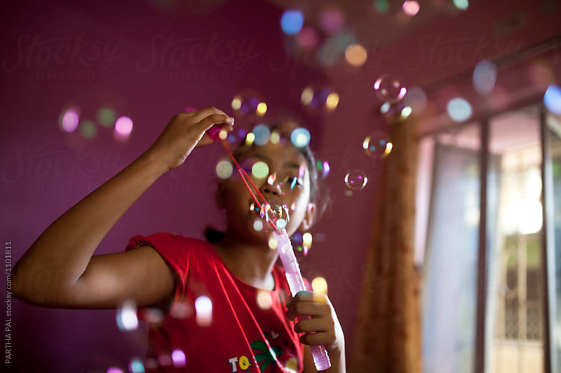 Teenage girl playing with bubble by PARTHA PAL for Stocksy United