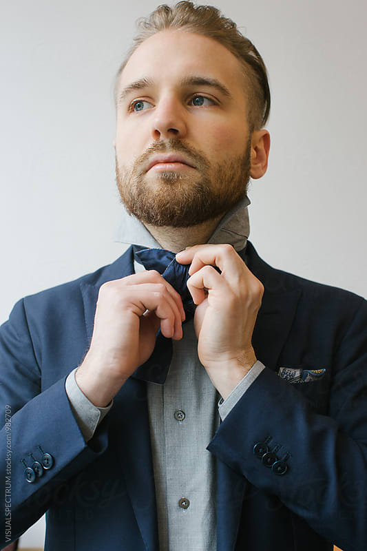 Men's Fashion - Indoor Portrait of Blond Caucasian Man Tying Bow Tie by Julien L. Balmer for Stocksy United