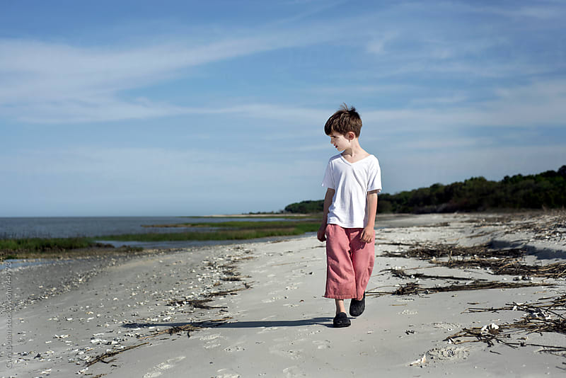 Boys walks on beach, looking out towards ocean by Cara Dolan for Stocksy United