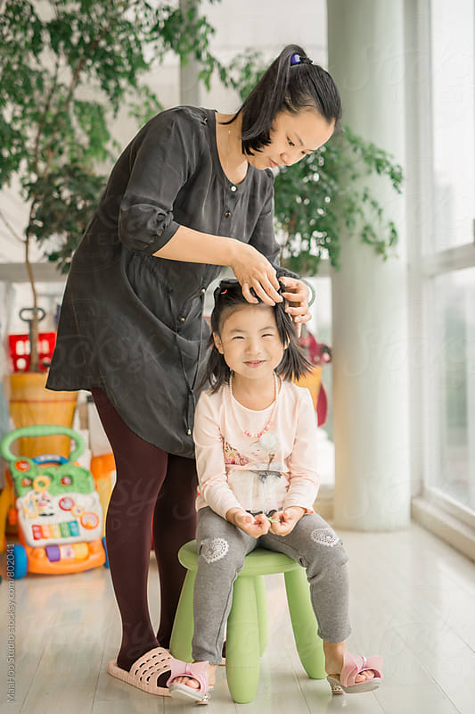Young mom brushing her daughter's hair  by Maa Hoo for Stocksy United