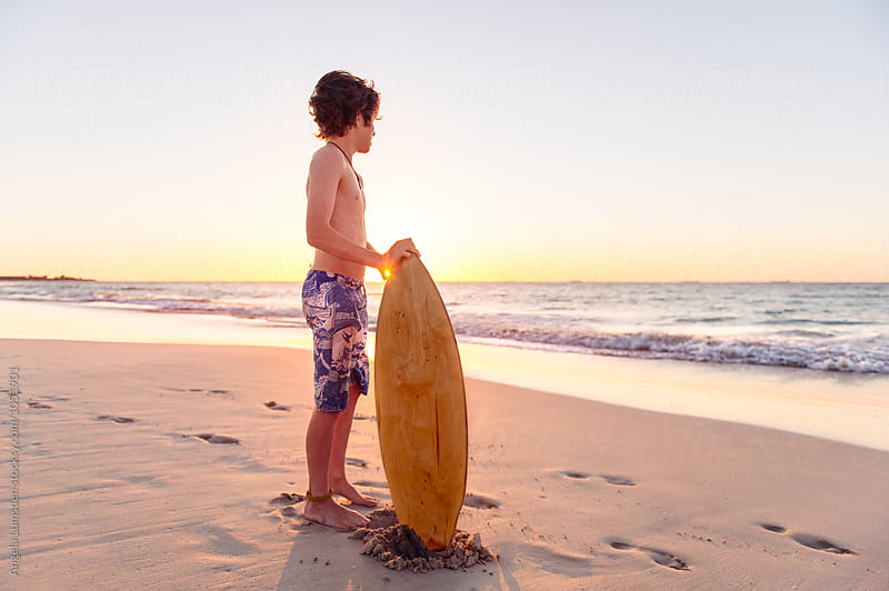 Boy standing with a skim board at the beach at sunset by Angela Lumsden for Stocksy United