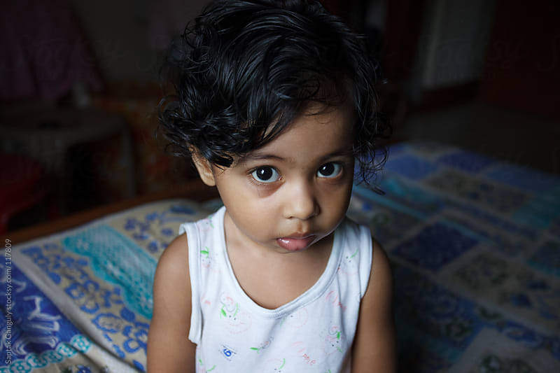 Cute baby girl looking very serious by Saptak Ganguly for Stocksy United