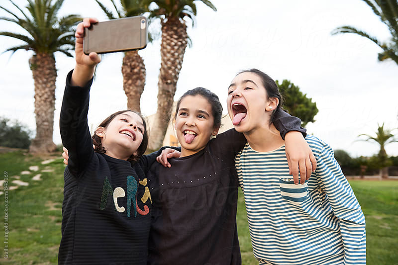 Three girls taking selfie  by Guille Faingold for Stocksy United