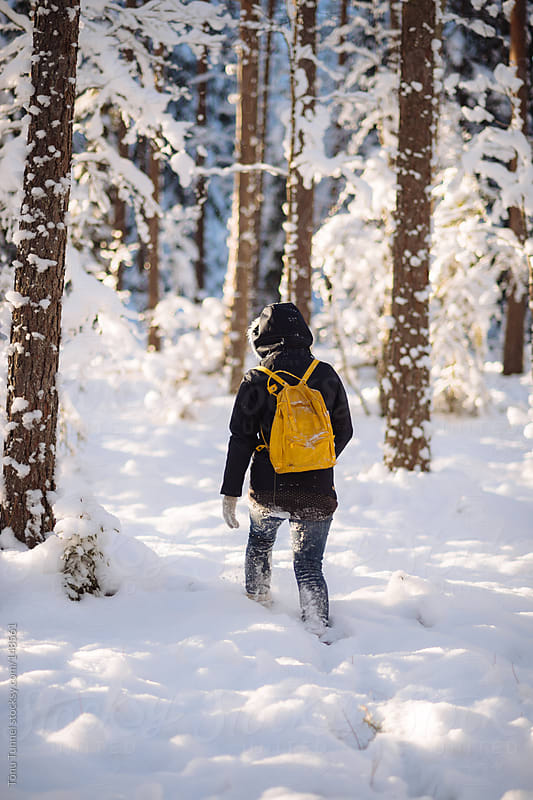 A scandinavian girl hiking in a snowy forest by Tõnu Tunnel for Stocksy United