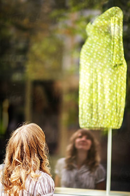 Young caucasian woman is standing near a shop window and looking at the summer green dress for pregnant women by Ilya for Stocksy United