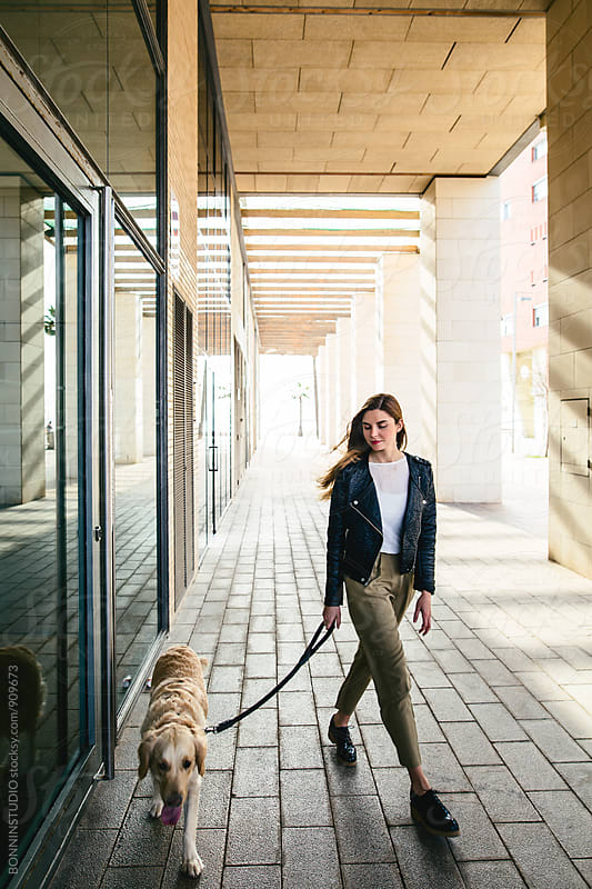 Young woman walking her dog on sidewalk. by BONNINSTUDIO for Stocksy United