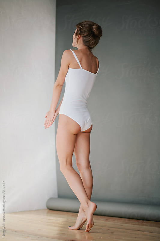 The girl in a white bathing suit posing on a gray background by Sergey Filimonov for Stocksy United