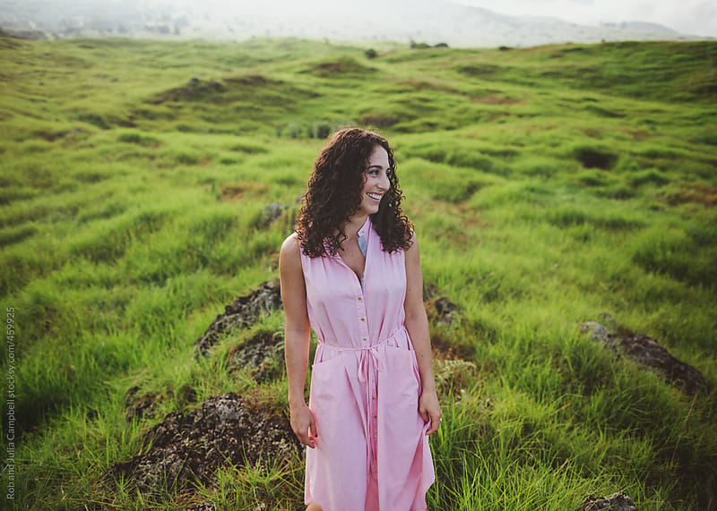 Beautiful woman with curly brown hair smiling outside in nature - candid by Rob and Julia Campbell for Stocksy United