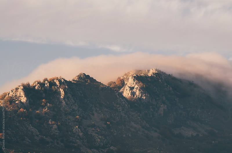 Mountain peak at sunset with fog by Cosma Andrei for Stocksy United