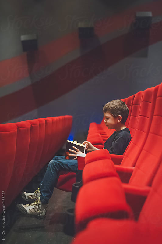 Young boy sitting alone in a movie theater waiting for a film to start and eating popcorn. by Lea Csontos for Stocksy United