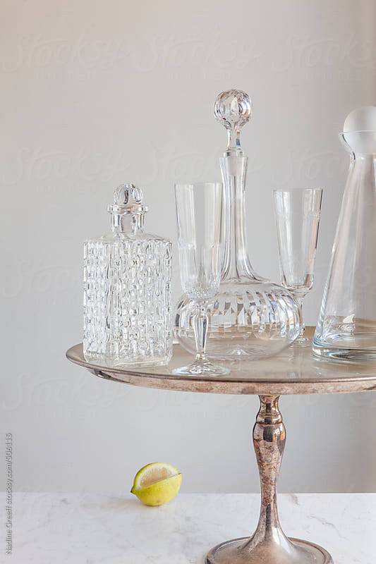 Cut glass crystal and modern whiskey, brandy decanters with champagne glasses by Nadine Greeff for Stocksy United