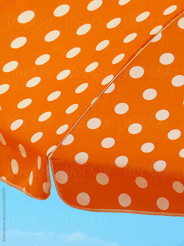 orange sun umbrella wit white dots by Sonja Lekovic for Stocksy United