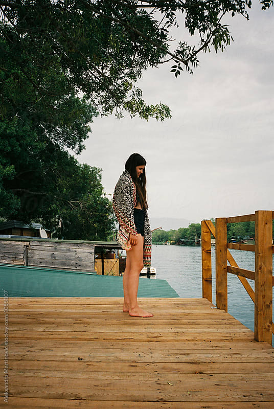 A girl on the stilt house by Aleksandra Martinovic for Stocksy United