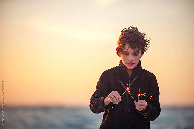 Boy playing with sparklers at the beach  by Angela Lumsden for Stocksy United