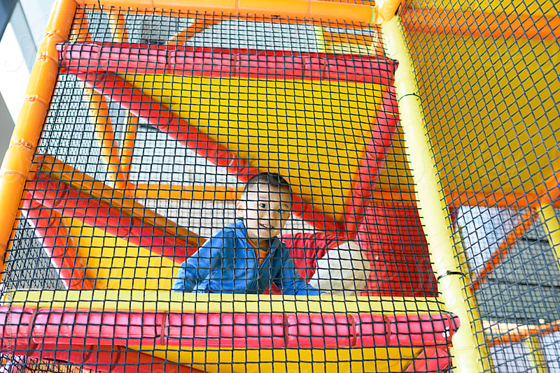 Boy playing behind net on playground by Lawren Lu for Stocksy United
