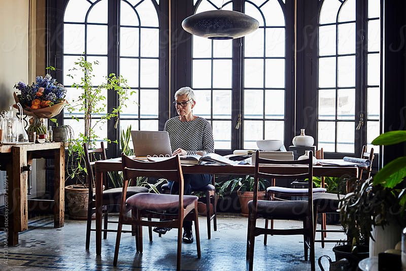 Senior Woman Using Laptop At Table In House by ALTO IMAGES for Stocksy United