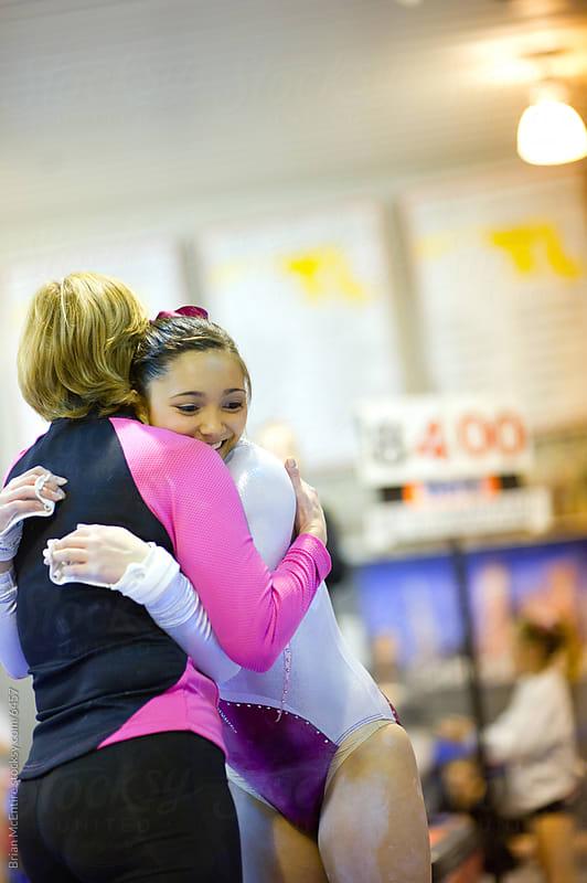 Gymnast Hugs Coach After Bars Routine by Brian McEntire for Stocksy United