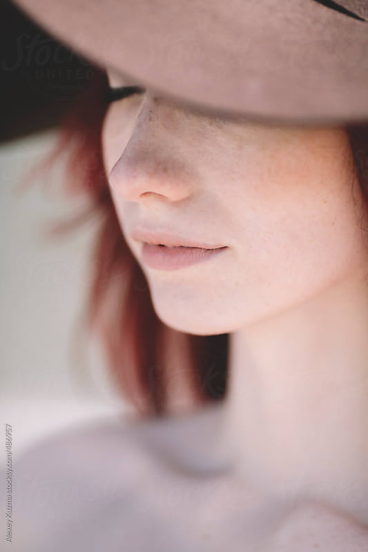 closeup of young dreaming woman with hat by Alexey Kuzma for Stocksy United