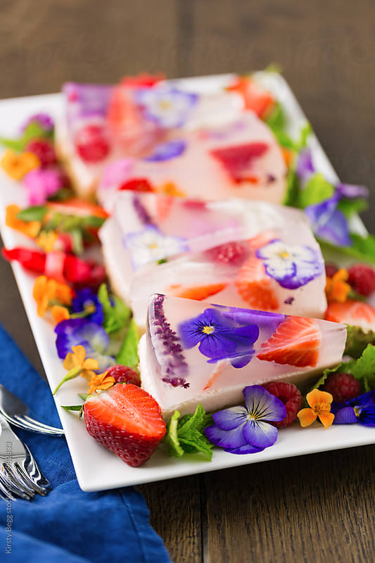 Vertical shot of jelly dessert slice with edible flowers by Kirsty Begg for Stocksy United