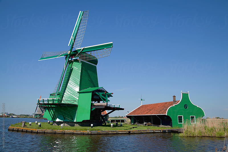 A classic windmill standing in the sun next to a green shed right along a dutch canal  by Ivo de Bruijn for Stocksy United