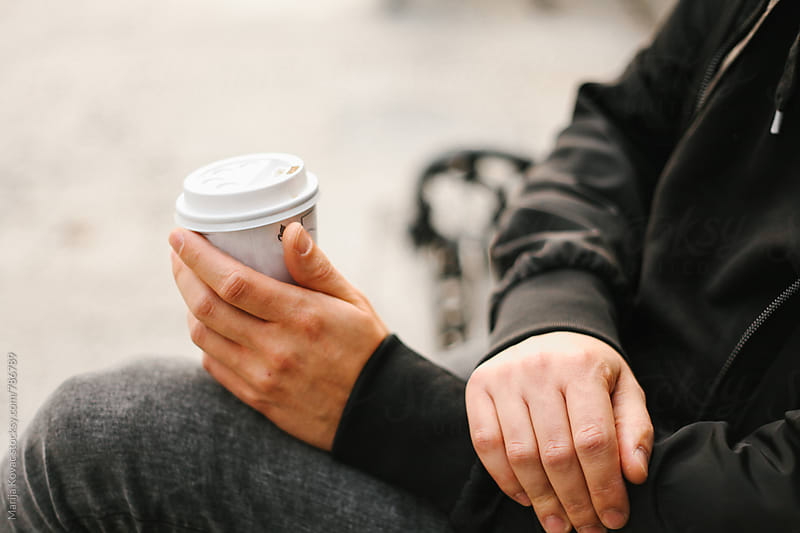 Male hand holding a coffee  by Marija Kovac for Stocksy United