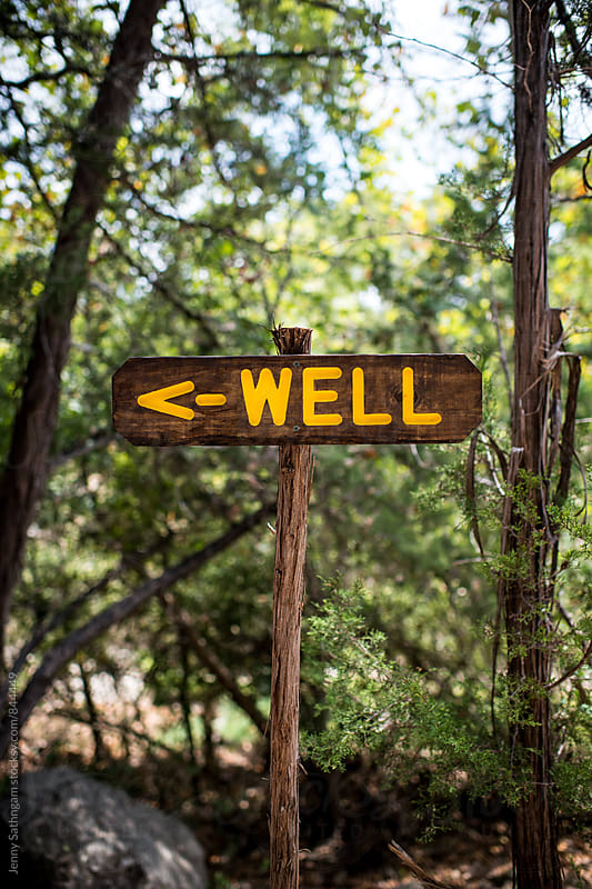 Trail sign pointing to a well by Jenny Sathngam for Stocksy United