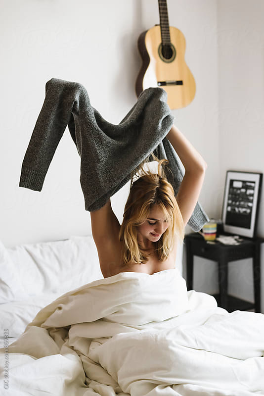 Young woman is wearing a sweater in the bed by WAVE for Stocksy United