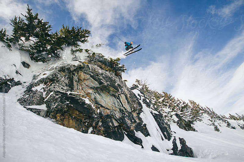 Skier jumping cliff in Whistler backcountry. Extreme ski  by Alejandro Moreno de Carlos for Stocksy United