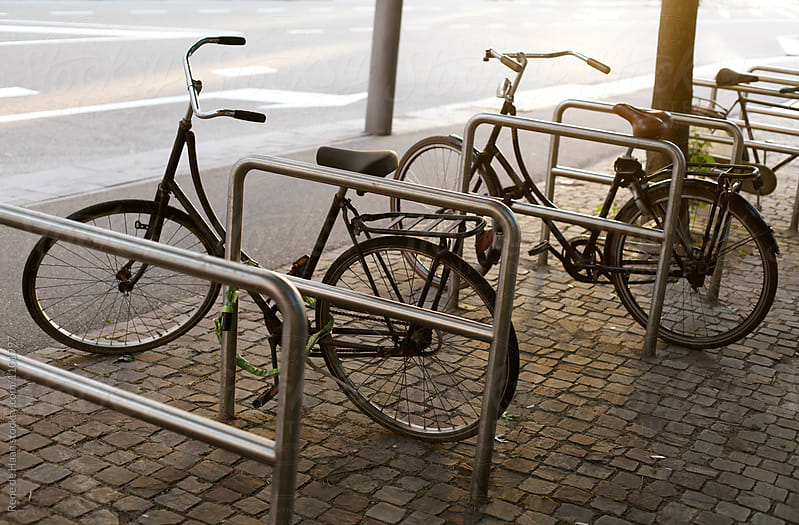 three bicycles in bicycle rack by Rene de Haan for Stocksy United