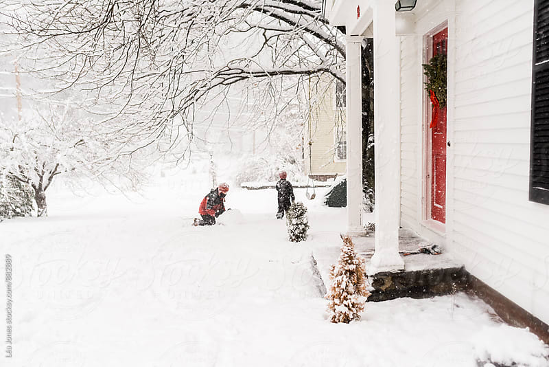 children playing in the snow in front of their house  by Léa Jones for Stocksy United