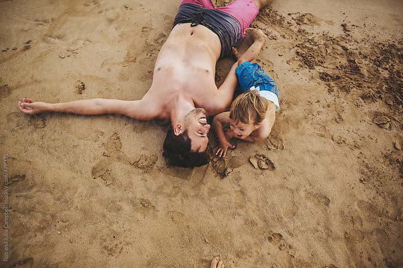 Young dad having fun lying down with toddler son on tropical beach by Rob and Julia Campbell for Stocksy United