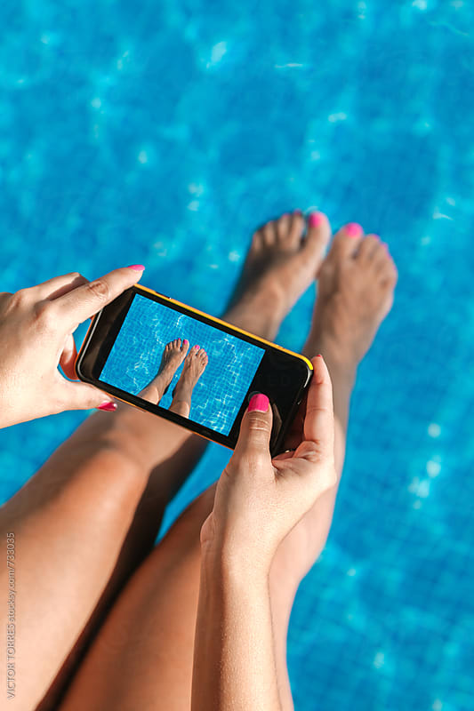 Woman in the Pool Taking a Photo of Her Feet with a Mobile Phone by VICTOR TORRES for Stocksy United