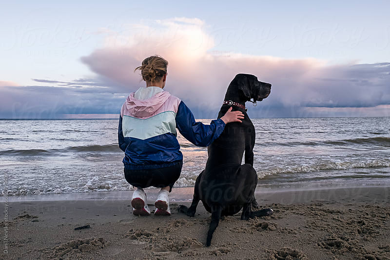 Back view of woman with pet on beach by Danil Nevsky for Stocksy United