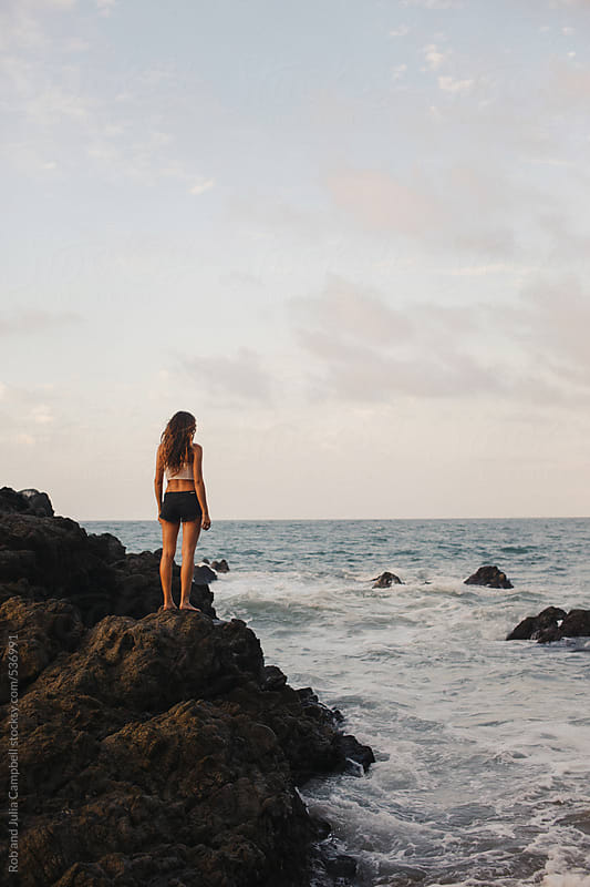 Pretty young girl standing on ocean rocks - looking out to sea by Rob and Julia Campbell for Stocksy United
