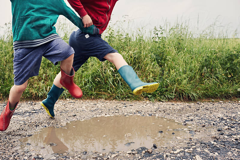 Children jumping in a muddy puddle by sally anscombe for Stocksy United