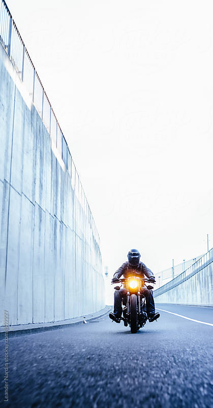 motorcyclist riding his bike in urban area by Leander Nardin for Stocksy United