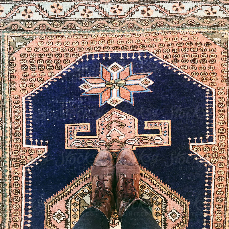 A woman looking down at her boots on a colorful vintage rug by Kristen Curette Hines for Stocksy United