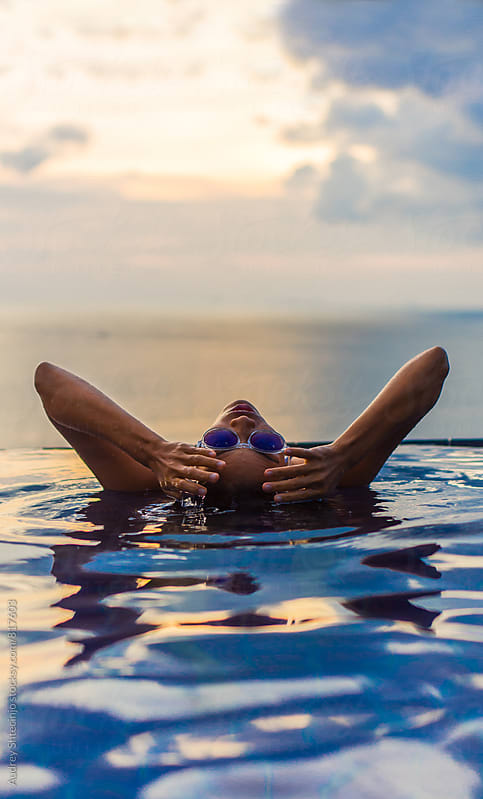 Woman enjoying swimming in the pool/horizon with sky and sea in background by Marko Milanovic for Stocksy United