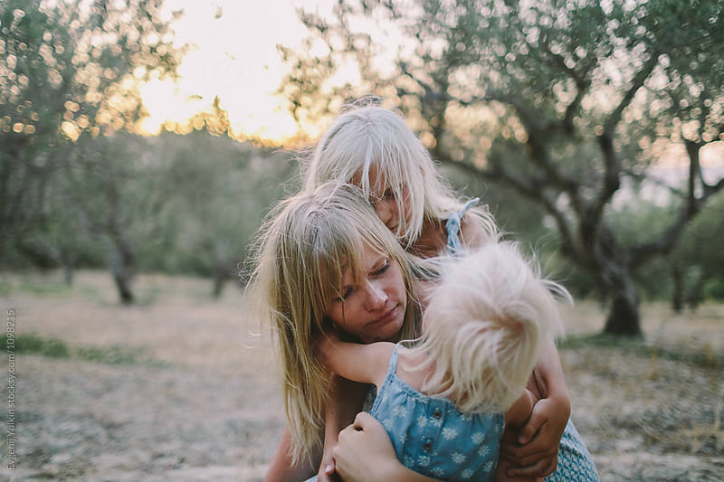 Little daughters embracing her mother by Evgenij Yulkin for Stocksy United