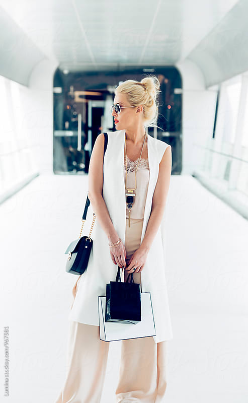 Blonde Woman Carrying Shopping Bags in the Shopping Mall by Lumina for Stocksy United