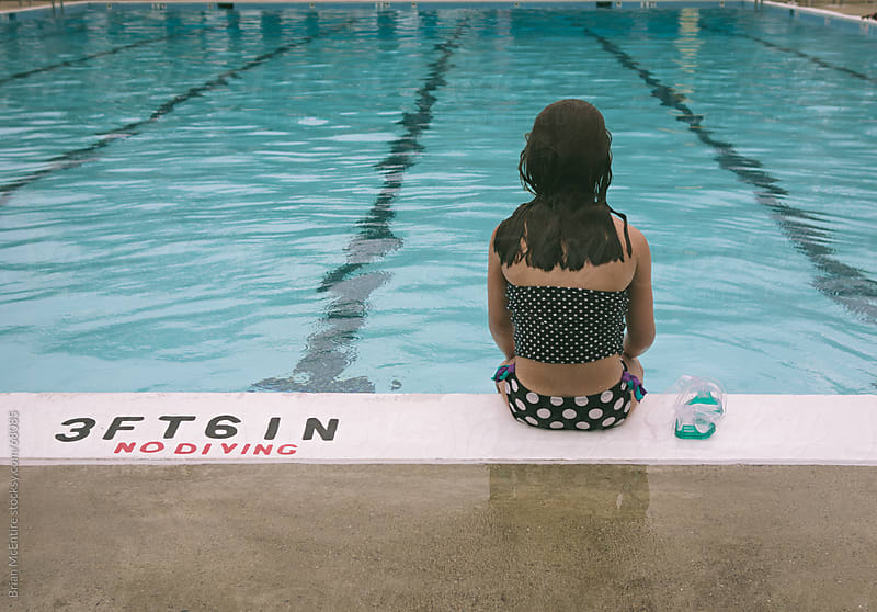 Girl Sitting at Edge of Pool on Rainy Day by Brian McEntire for Stocksy United