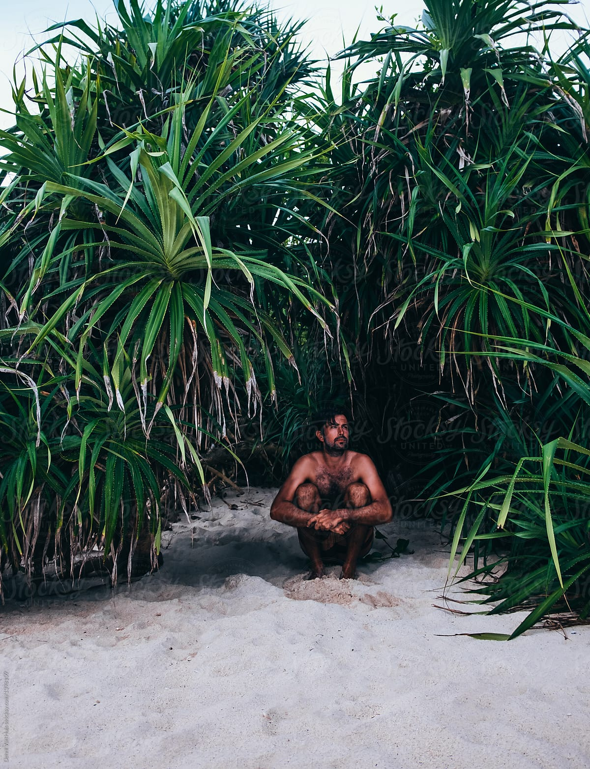 Man Finding Shelter In The Shade Under Tropical Plants On The