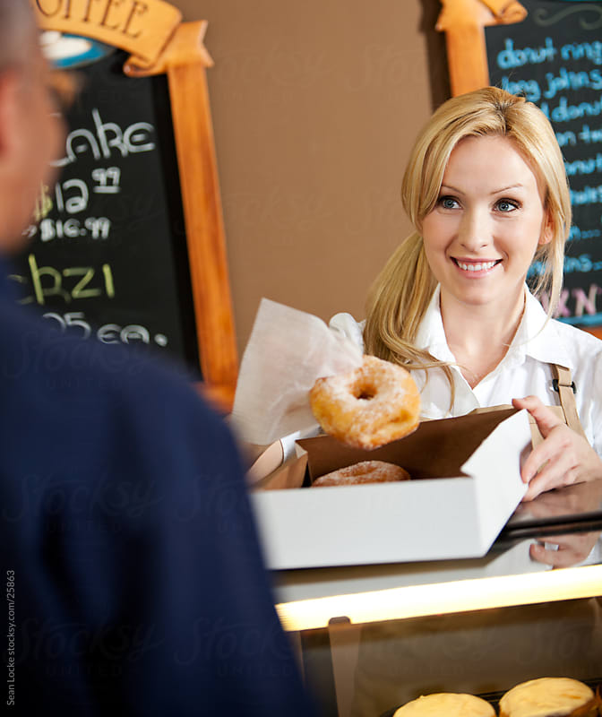 Bakery: Employee Boxing Up Donuts for Customer by Sean Locke for Stocksy United